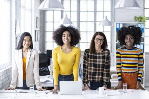 female team standing in modern workplace and looking at camera
