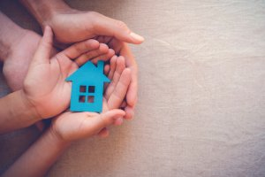 adult and child hands holding a paper house