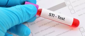 gloved hand holding a vial labeled STI Test