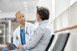 male doctor counseling patient in waiting room